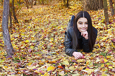 Teenager laying on leaves
