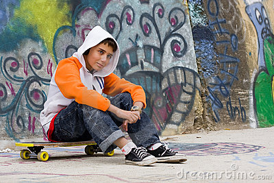 Teenager listening music near a graffiti wall