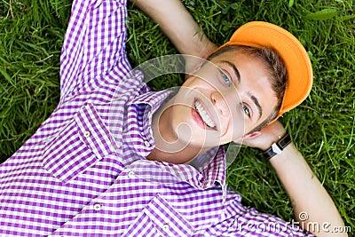 Teenager lying down on grass