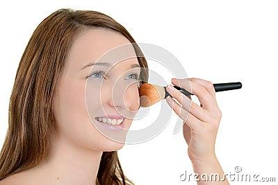 Teenager putting on blush