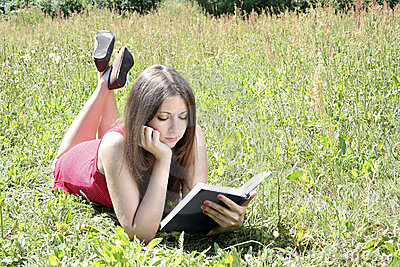 Teenager reading book in field