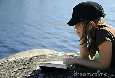 Teenager reading a book outdoor