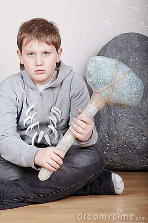 Teenager sits with unkind face with stone ax
