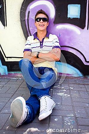 Teenager sitting against graffiti wall