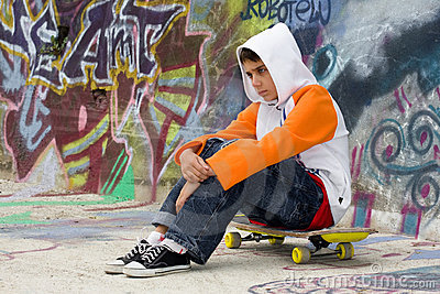Teenager sitting near a graffiti wall