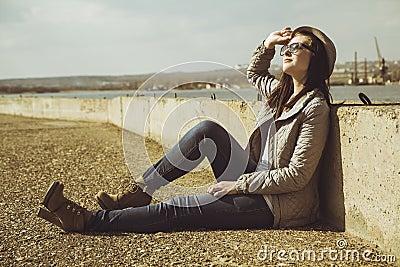 Teenager in sitting on sidewalk