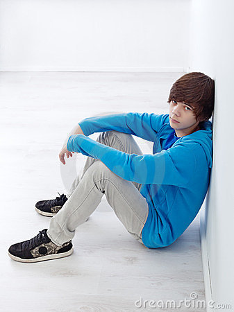 Teenager sitting by the wall