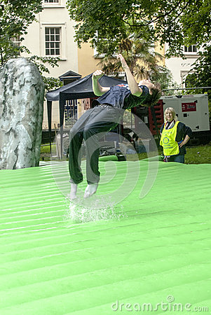 Teenager summersaulting on inflatable Stonehenge Editorial Photo