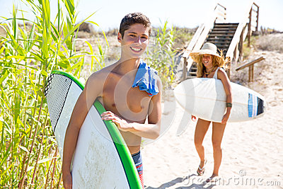 Teenager surfers waling to the beach