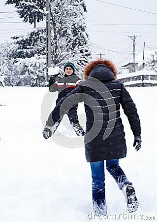 Teenager throwing snowballs