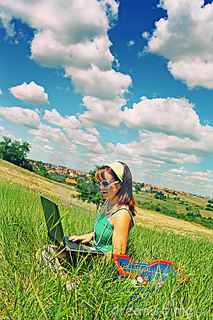 Teenager using laptop in field
