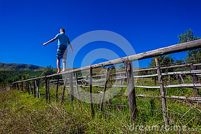 Teenager Walking Balancing Fence