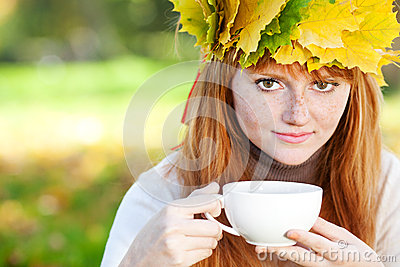 Teenager woman in a wreath of maple leaves with cu