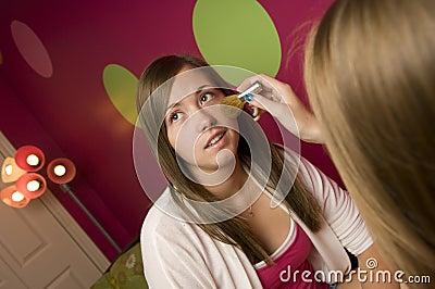 Teenagers applying makeup