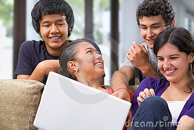 Teenagers discussing something on laptop
