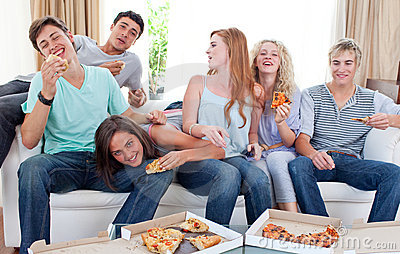 Teenagers eating pizza at home