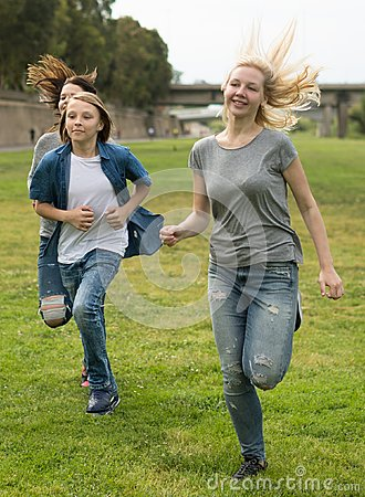 Free Teenagers Running Through Green Lawn In Summer In Park Stock Photos - 100848643