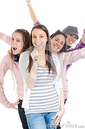 Teenagers singing on microphones in line