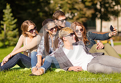 Teenagers taking photo outside with smartphone