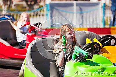 Happy teen girl driving bumper car