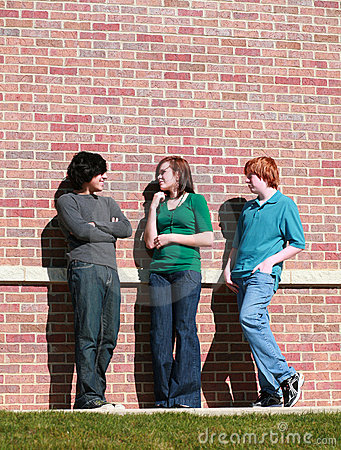 Teens in front of brick wall