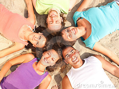 Teens lying on a beach in a circle