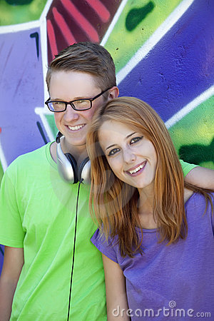 Teens near graffiti wall.