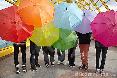 Teens with opened umbrellas in pedestrian overpass