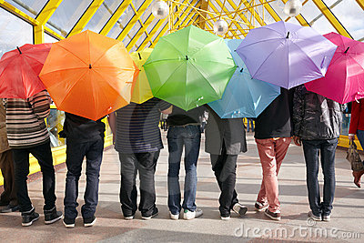 Teens with opened umbrellas. rainbow concept