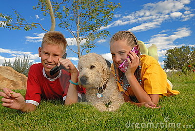 Teens with phones and dog