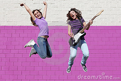 Teens playing guitar jumping