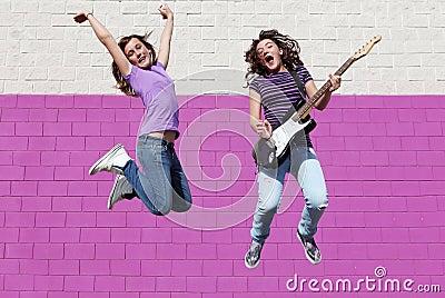 Teens playing guitar jumping