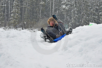 Teens sledding on a saucer