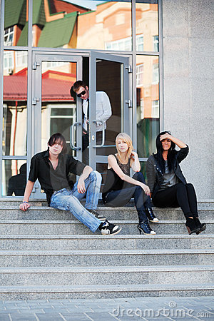 Group of young fashion people sitting on the steps