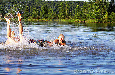 Teens swim and play on the laugh at a river