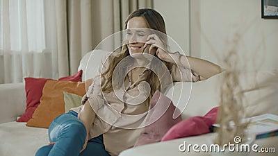 Telefono felice di chiamata della donna sul sofà a casa Telefono cellulare di conversazione sorridente della donna stock footage