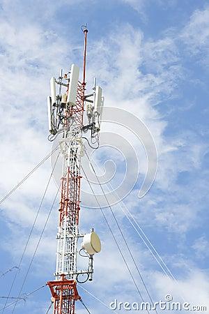 Telefonu komórkowego komunikacyjny wierza przeciw niebieskiemu niebu.