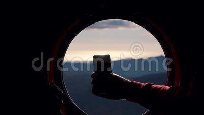 A telephone shot at a helicopter window in the mountains stock footage