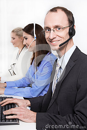 Telesales or helpdesk team - helpful man with headset smiling at