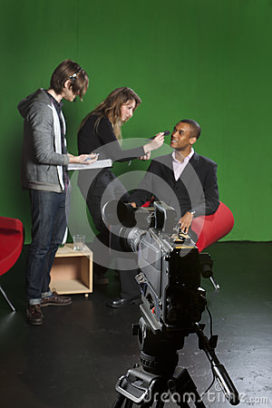 Television camera on tripod in studio with crew in