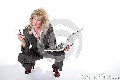 Teléfono celular y computadora portátil que hacen juegos malabares de la mujer de negocios