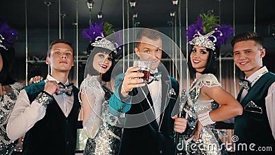 Tematu przyjęcie - ludzie w lśnić retro ubrania stoją bezczynnie ich przyjaciela szkło napój którego w górę podnosi zdjęcie wideo