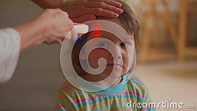 Temperatura del niño enfermo por termómetro no de contacto metrajes