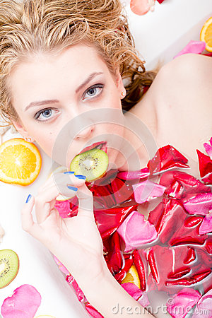 Free Tempting Beautiful Young Blond Sexy Woman In A Bath With Flower Petals Biting Piece Of Kiwi Closeup Portrait Royalty Free Stock Image - 39856946