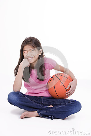 Ten year old Asian girl holding basketball