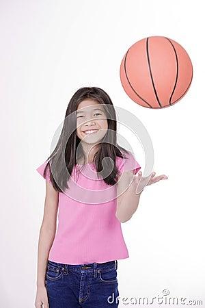 Ten year old girl throwing basketball,
