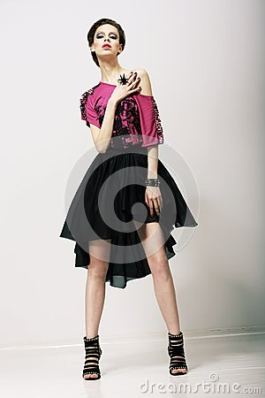 Tendency. Glamorous Fashion Model in Modern Clothes posing in Studio