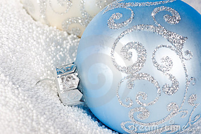Tender blue Christmas bauble on to snow.