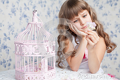 Tender dreamy romantic girl near open birdcage