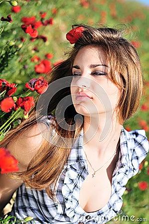 Tender girl in field of poppy